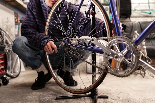 Mann, der fahrrad mit schraubenschlüssel nah oben repariert