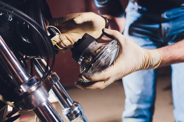 Mann, der fahrrad repariert. zuversichtlich junger mann, der motorrad nahe seiner garage repariert. ersatzlampe im scheinwerfer