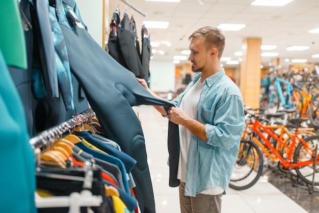 Mann, der fahrradanzug wählt, einkaufen im sportgeschäft.