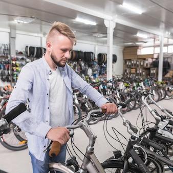 Mann, der fahrradlenker im shop justiert
