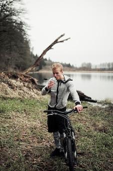 Mann, der fahrradtrinkwasser von der flasche hält