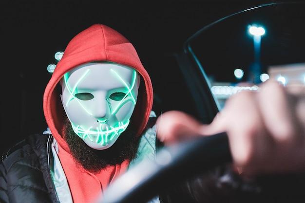 Mann, der fahrzeug mit maske nachts fährt