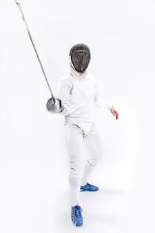 Mann, der fechtanzug trägt, der mit schwert gegen grau übt