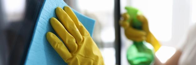 Mann, der fenster in der schutzhandschuhenahaufnahme wäscht. wohnungsreinigung konzept