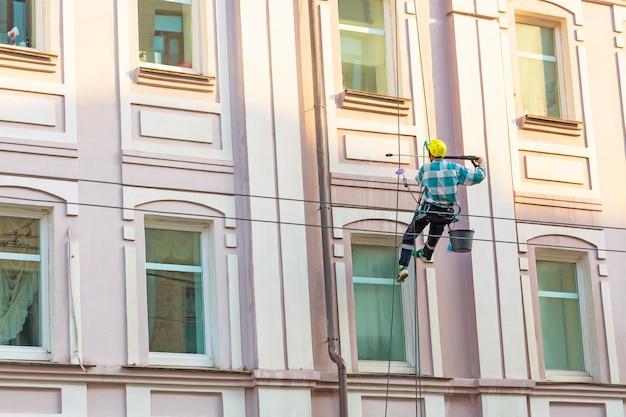 Mann, der fenster und wand auf altstadtgebäude reinigt