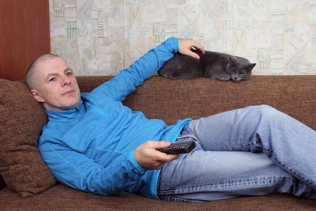 Mann, der fernsieht und sich auf der couch mit der katze entspannt