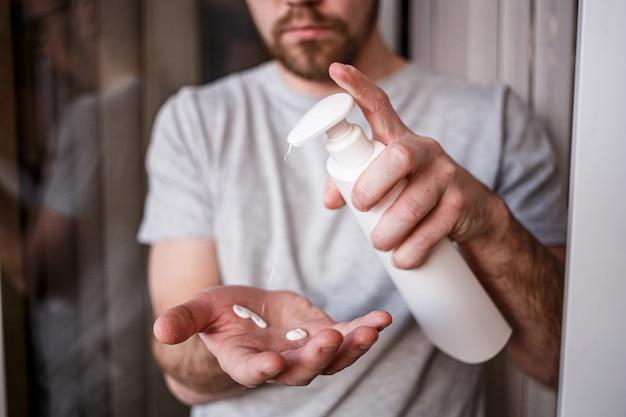Mann, der feuchtigkeitslotion aufträgt, die von der flasche auf seine hand mit sehr trockener haut mit creme wegen des waschens von alkohol fällt