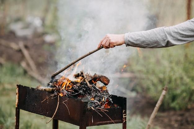 Mann, der feuer für grill im hinterhof macht
