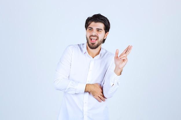 Mann, der fingerkreuzzeichen zeigt und fluchend