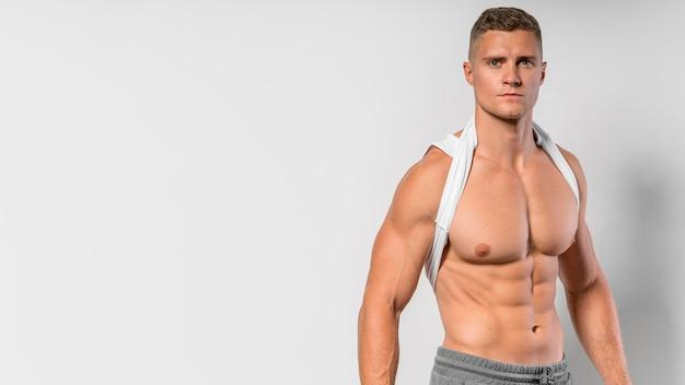 Mann, der fit körper zeigt, während er mit kopienraum aufwirft