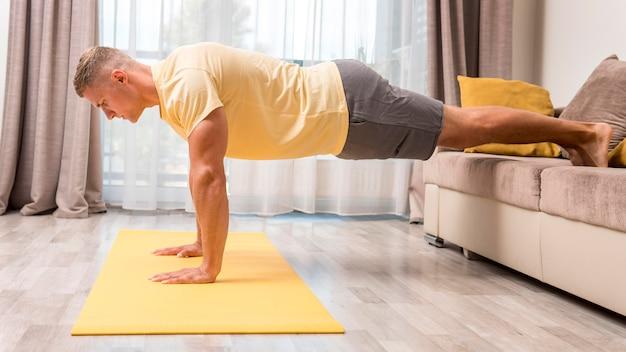 Mann, der fitness zu hause auf matte tut