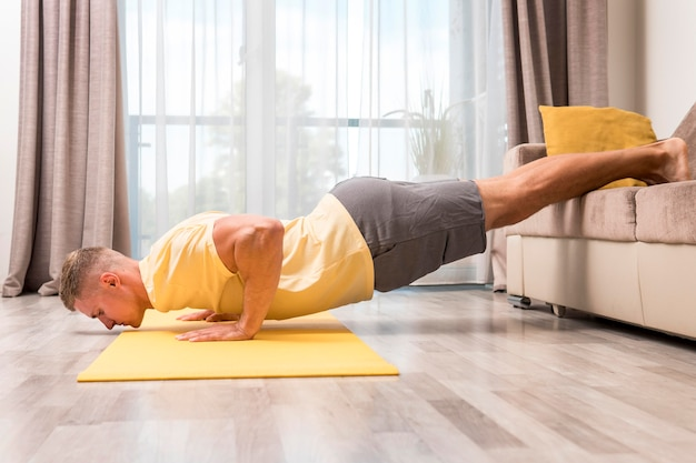 Mann, der fitness zu hause mit couch tut