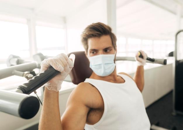 Mann, der fitnessgeräte beim tragen der medizinischen maske verwendet