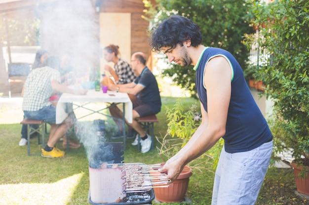 Mann, der fleisch auf dem grill kocht