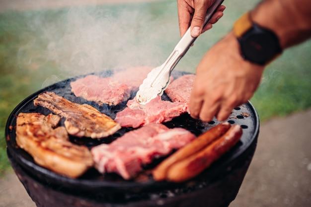 Mann, der fleisch auf grill grillt