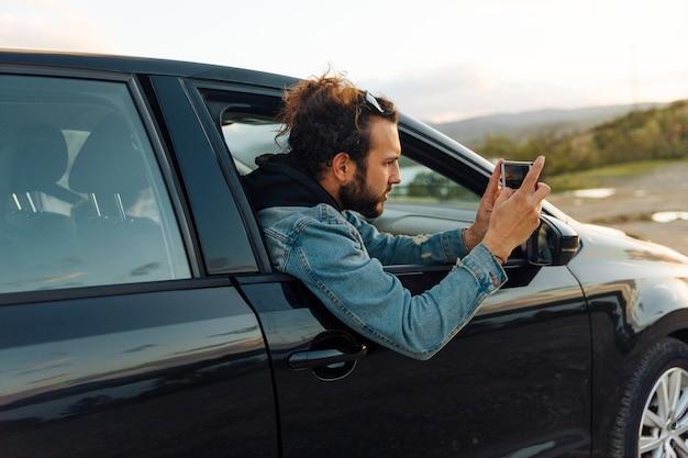 Mann, der foto am telefon auf reise macht