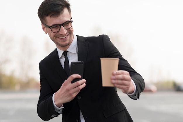 Mann, der foto der kaffeetasse nimmt