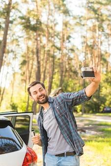 Mann, der foto nahe bei auto macht