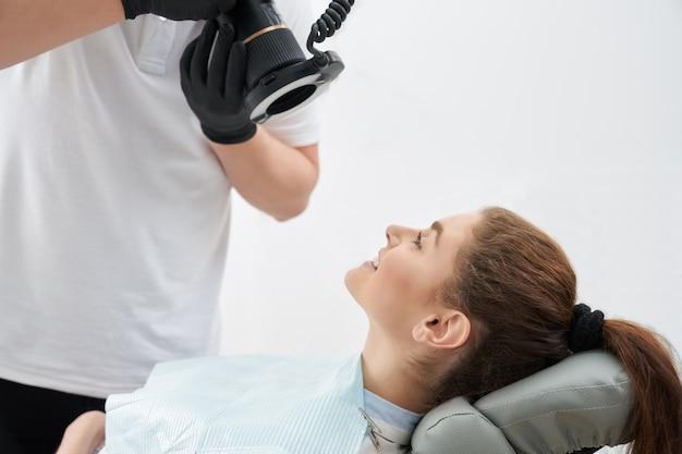 Mann, der foto von zähnen nach dem aufhellen in der zahnarztpraxis nimmt