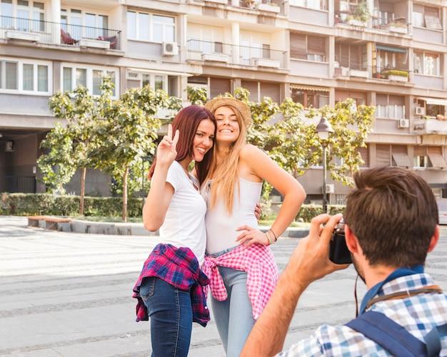 Mann, der foto von zwei glücklichen frauen auf kamera macht