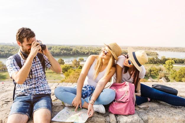 Mann, der foto von zwei glücklichen freundinnen auf kamera macht
