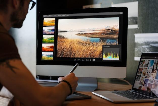 Mann, der fotos auf einem computer redigiert
