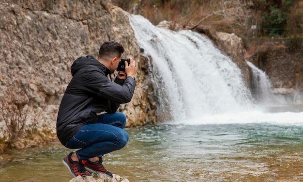Mann, der fotos der natur macht Kostenlose Fotos