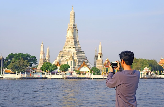 Mann, der fotos vom tempel der morgenröte oder wat arun, dem ikonischen wahrzeichen am ufer des flusses chao phraya, bangkok, thailand, macht