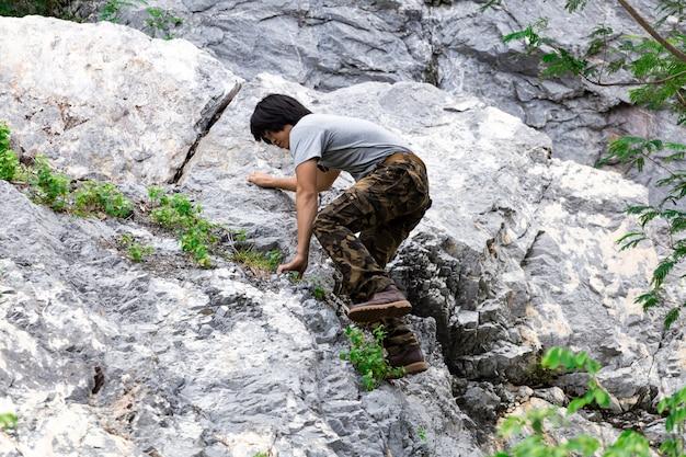 Mann, der frachthosen trägt und auf dem felsen klettert