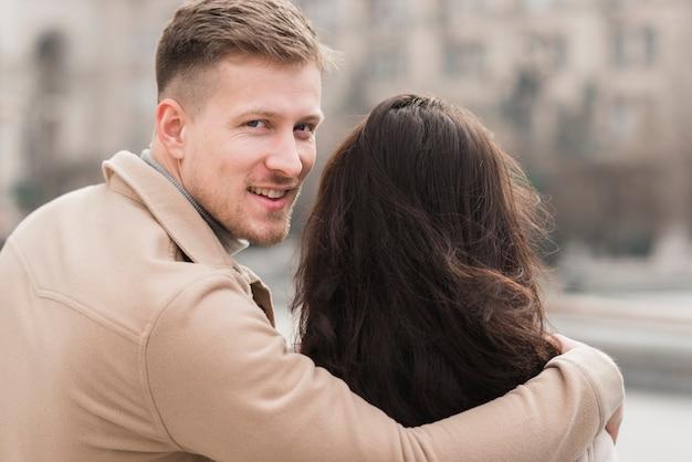 Mann, der frau beim aufstellen umarmt