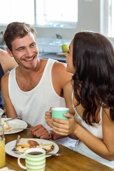 Mann, der frau beim zu hause frühstücken betrachtet