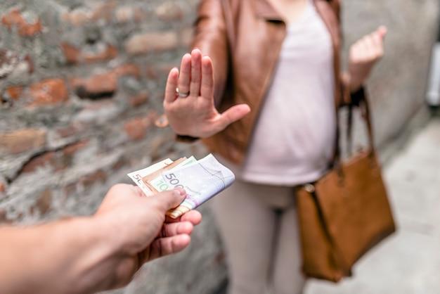 Mann, der frau für sex zahlt. frau, die sich weigert, bestechungsgeld zu nehmen, konzept der bestechung und bestechung