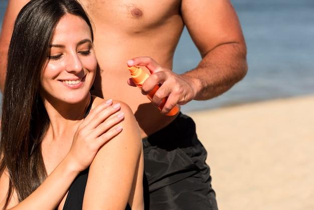 Mann, der frau hilft, sonnenschutz am strand anzuwenden