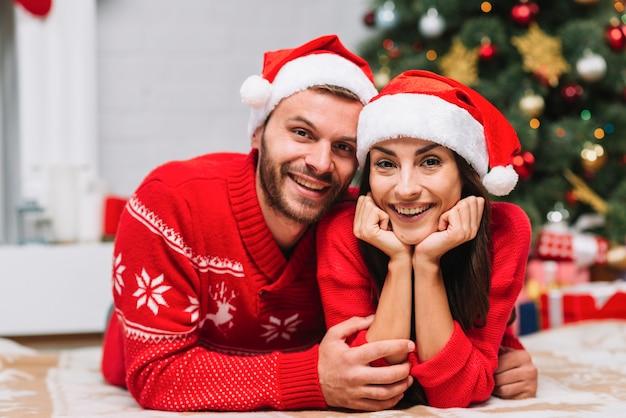 Mann, der frau nahe weihnachtsbaum umarmt