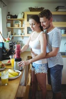 Mann, der frau von hinten umarmt, während wassermelonen-smoothie in der küche vorbereitet