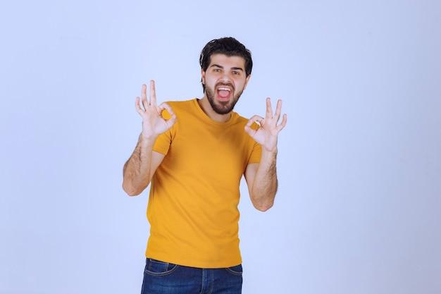 Mann, der freude und ok handzeichen zeigt