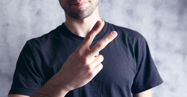Mann, der friedenszeichen mit handgeste zeigt