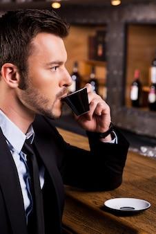 Mann, der frischen kaffee genießt seitenansicht eines selbstbewussten jungen mannes in abendgarderobe, der an der bartheke sitzt und kaffee trinkt