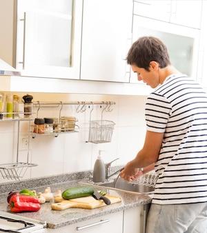 Mann, der frischgemüse in der küchenwanne säubert