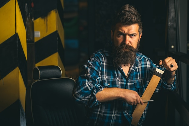Mann, der friseur im friseurladen besucht. borten. friseur, der einen bärtigen mann in einem friseurladen rasiert. er ist