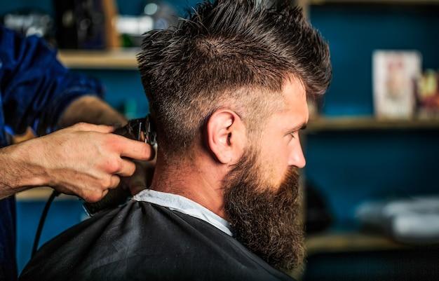 Mann, der friseur im friseursalon besucht. barber arbeitet mit haarschneider