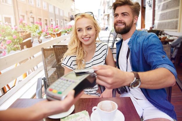 Mann, der für den kaffee mit einer kreditkarte bezahlt
