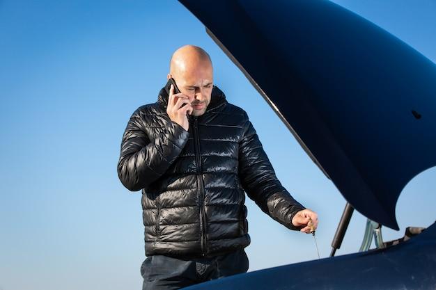 Mann, der für straßendienst, autounterstützung mit seinem auto am straßenrand, autoproblem, problem, transportkonzept aufruft