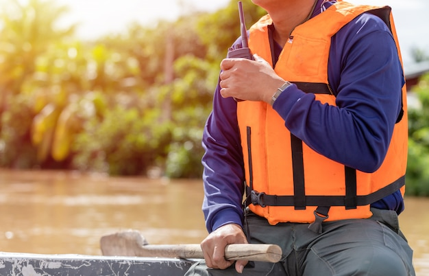 Mann, der funksprechgerät auf dem boot verwendet