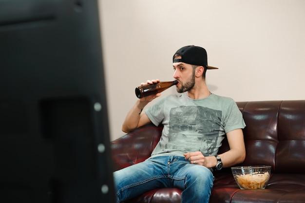 Mann, der fußball beobachtet und bier trinkt, fußballfan