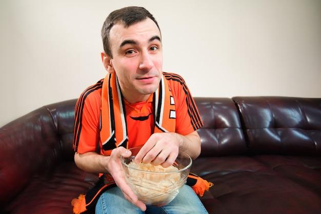 Mann, der fußball beobachtet und chips isst, fußballfan