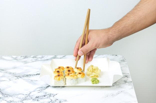 Mann, der gebackenes sushi im take-away-behälter isst