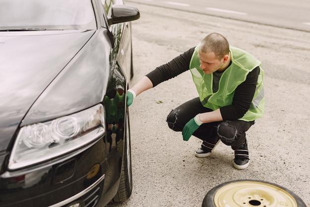 Mann, der gebrochenes rad am auto wechselt