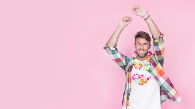 Mann, der gefälschte blumengirlande um sein halstanzen gegen rosa hintergrund trägt