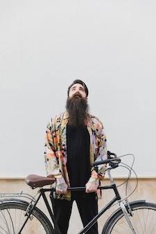 Mann, der gegen die wand hält das fahrrad oben schaut steht
